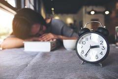 Mujer asiática que toma una siesta mientras que lee un libro con el despertador negro en la tabla fotos de archivo