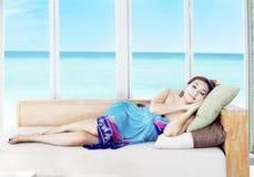 Mujer asiática que toma una siesta por la playa Imagenes de archivo