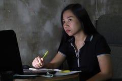 Mujer asiática que trabaja del hogar atrasado en el trabajo nocturno en concepto de iluminación pobre la luz oscura tiene cierto  foto de archivo libre de regalías