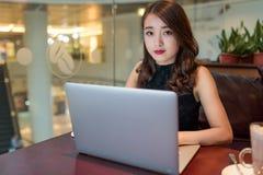 Mujer asiática que trabaja en el ordenador portátil Imagen de archivo