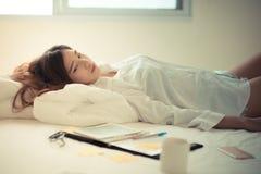 Mujer asiática que trabaja en la cama Imagenes de archivo