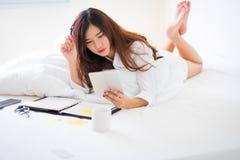 Mujer asiática que trabaja en la cama Fotos de archivo