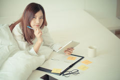 Mujer asiática que trabaja en la cama Foto de archivo libre de regalías