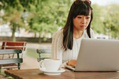 Mujer asiática que trabaja en un ordenador portátil en el café Fotografía de archivo libre de regalías