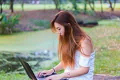 Mujer asiática que trabaja en un ordenador portátil en un jardín o un parque Fotos de archivo libres de regalías