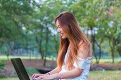 Mujer asiática que trabaja en un ordenador portátil que sonríe en un jardín o un parque Fotografía de archivo