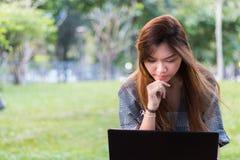 Mujer asiática que trabaja en un ordenador portátil y que piensa en un jardín o un parque Fotos de archivo