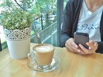 Mujer asiática que trabaja por smartphone con la taza de café Imagenes de archivo