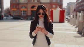 Mujer asiática que usa el app en smartphone en ciudad almacen de metraje de vídeo
