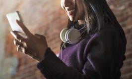 Mujer asiática que usa el dispositivo y los auriculares digitales foto de archivo