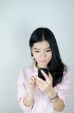 Mujer asiática que usa smartphone Fotografía de archivo
