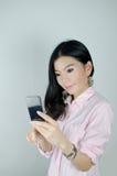 Mujer asiática que usa smartphone Foto de archivo libre de regalías