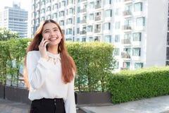 Mujer asiática que usa el teléfono elegante en el fondo borroso del residenti Foto de archivo
