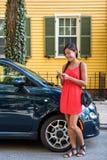 Mujer asiática que usa el teléfono móvil app para la distribución de coche Imagenes de archivo