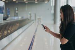 Mujer asiática que usa el teléfono móvil con la sensación cara feliz y sonriente, situación y para demanda de equipaje que espera fotografía de archivo libre de regalías