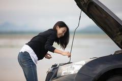 Mujer asiática que usa el teléfono móvil mientras que mira y hombre subrayado si fotografía de archivo