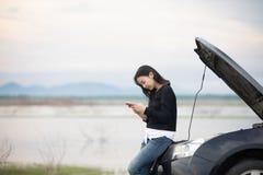 Mujer asiática que usa el teléfono móvil mientras que mira y hombre subrayado si foto de archivo