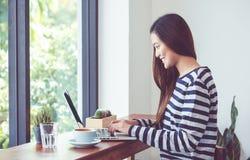 Mujer asiática que usa en el ordenador portátil cerca de ventana en el restaur del café Fotos de archivo libres de regalías