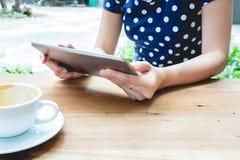 Mujer asiática que usa la PC de la tableta en una tabla de madera Fotografía de archivo