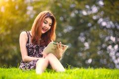 Mujer asiática que usa la tableta digital en parque Fotos de archivo libres de regalías