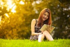 Mujer asiática que usa la tableta digital en parque Imágenes de archivo libres de regalías