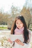 Mujer asiática que usa la tableta digital en parque Foto de archivo libre de regalías