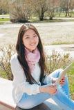 Mujer asiática que usa la tableta digital en parque Foto de archivo