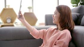 Mujer asiática que usa la tableta mientras que miente en el sofá casero en su sala de estar Tableta femenina feliz del uso para l almacen de video