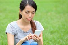 Mujer asiática que usa smartphone Imagen de archivo libre de regalías
