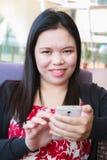 Mujer asiática que usa smartphone Imagen de archivo