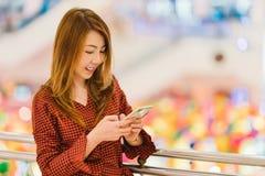 Mujer asiática que usa smartphone en la alameda de compras, fondo del bokeh de la falta de definición con el espacio de la copia Imagen de archivo