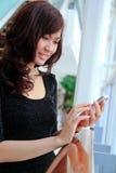 Mujer asiática que usa un teléfono celular Fotografía de archivo libre de regalías