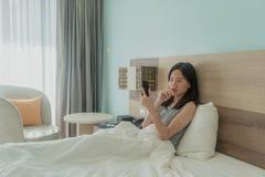 Mujer asiática que usa un teléfono móvil, pensando en problemas y sufriendo de la depresión en cama en un dormitorio moderno con  fotos de archivo