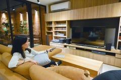 Mujer asiática que usa un teledirigido para girar la TV con el scre en blanco imagen de archivo