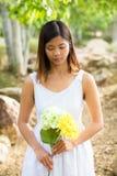 Mujer asiática sana en el vestido blanco que celebra las flores y las frutas en el parque verde Imagenes de archivo