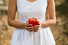 Mujer asiática sana en el vestido blanco que celebra las flores y las frutas en el parque verde Foto de archivo libre de regalías