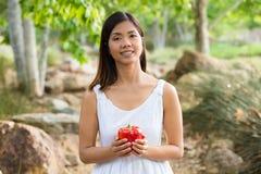 Mujer asiática sana en el vestido blanco que celebra las flores y las frutas en el parque verde Foto de archivo