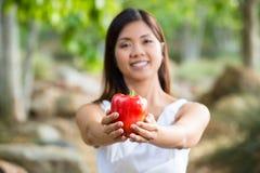 Mujer asiática sana en el vestido blanco que celebra las flores y las frutas en el parque verde Imágenes de archivo libres de regalías