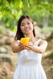 Mujer asiática sana en el vestido blanco que celebra las flores y las frutas en el parque verde Imagen de archivo libre de regalías