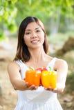 Mujer asiática sana en el vestido blanco que celebra las flores y las frutas en el parque verde Fotografía de archivo