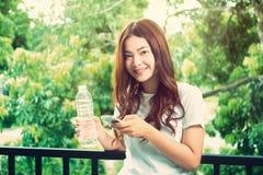 Mujer asiática sana hermosa joven feliz que sostiene la botella clara o foto de archivo