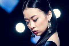 Mujer asiática sensual que presenta en pendientes del diamante en el evento con los proyectores Foto de archivo libre de regalías