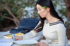 Mujer asiática seria que marca el texto en el cuaderno, asistiendo Imagen de archivo