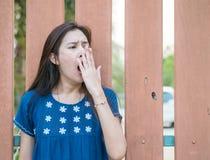 Mujer asiática soñolienta con el movimiento del bostezo en fondo de madera borroso de la cerca foto de archivo