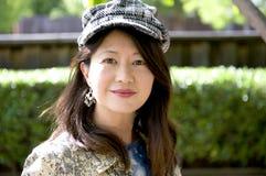 Mujer asiática sonriente con el casquillo de la raspa de arenque Imagenes de archivo