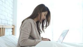 Mujer asiática sonriente de los jóvenes hermosos que trabaja en el ordenador portátil mientras que se sienta en cama en dormitori almacen de video