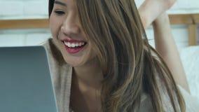 Mujer asiática sonriente de los jóvenes hermosos que trabaja en el ordenador portátil mientras que se sienta en cama en dormitori almacen de metraje de vídeo