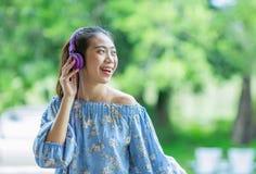 Mujer asiática sonriente de los jóvenes que escucha la música con los auriculares Imágenes de archivo libres de regalías