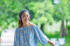Mujer asiática sonriente de los jóvenes que escucha la música con los auriculares Foto de archivo