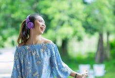 Mujer asiática sonriente de los jóvenes que escucha la música con los auriculares Imagenes de archivo